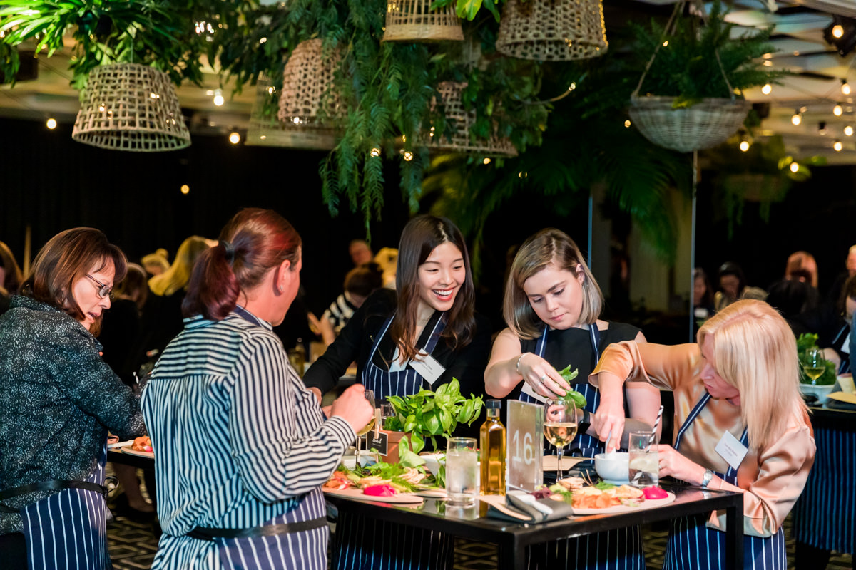 Corporate Event Photography - Group of people working together in a cooking class at the Daltone House Sydney