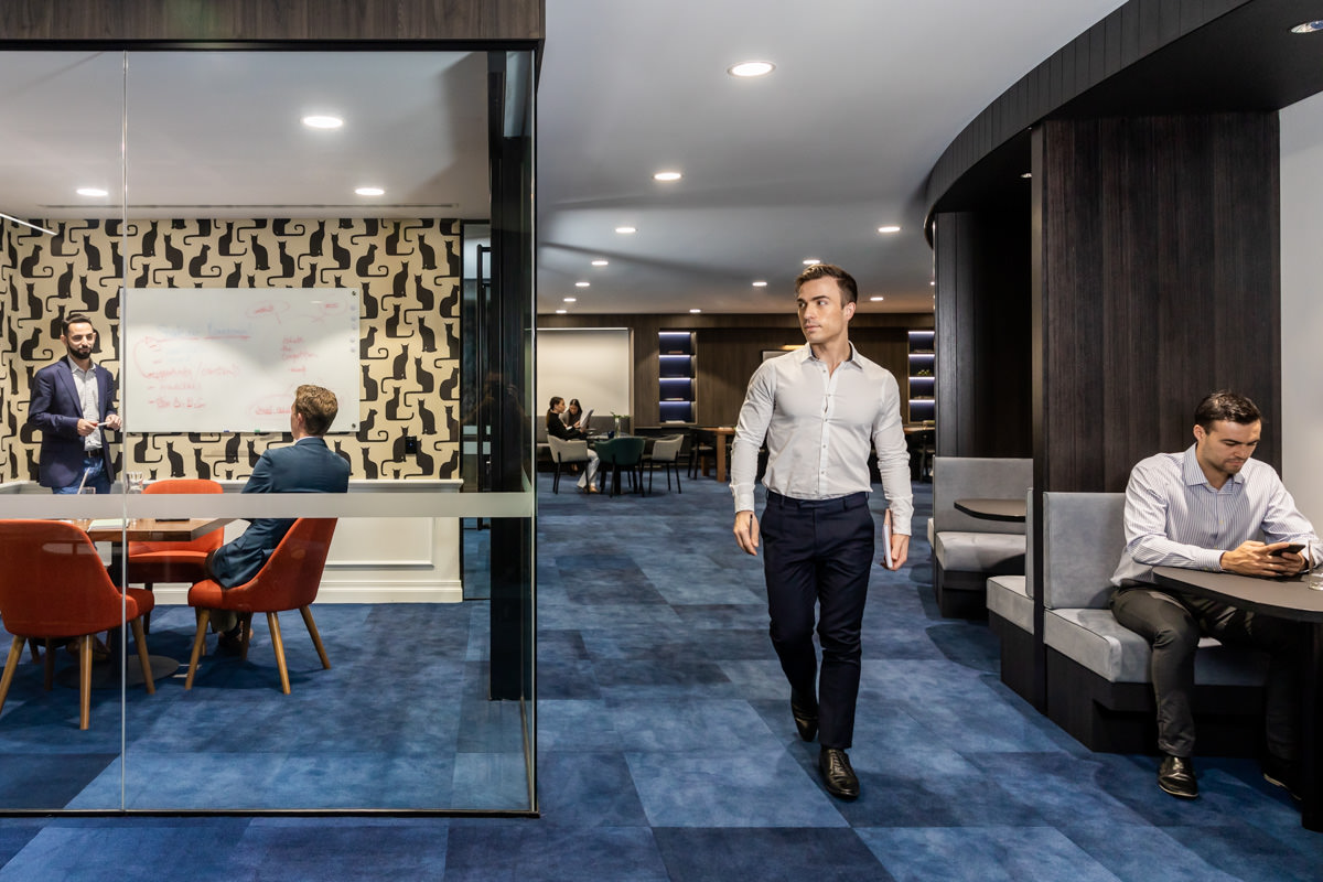 Corporate Lifestyle Photography - Man walking through common area in office